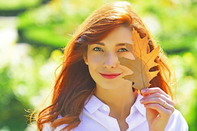 Fashion autumn young woman holds yellow maple leaves on fall park background.