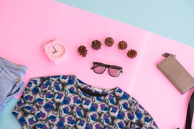 Fashion background concept. women's shirt, blue pants, women's bag on multi-colored pastel paper background