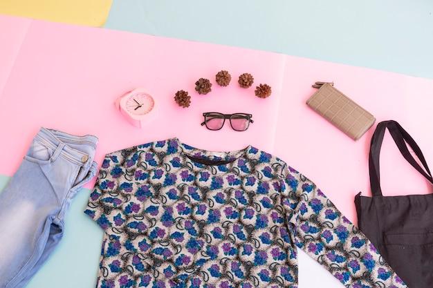 패션 배경 개념입니다. 여성용 셔츠, 파란색 바지, 다양한 색상의 파스텔 종이 배경에 여성용 가방