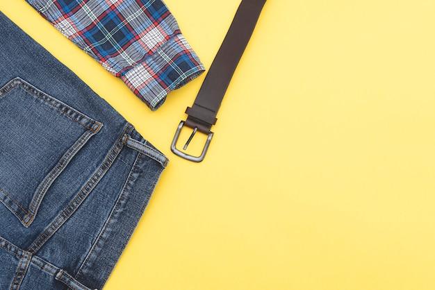 Предпосылка моды, джинсы, рубашка, пояс. джинсовый стиль. вид сверху. мужская одежда на желтом фоне, место для текста.