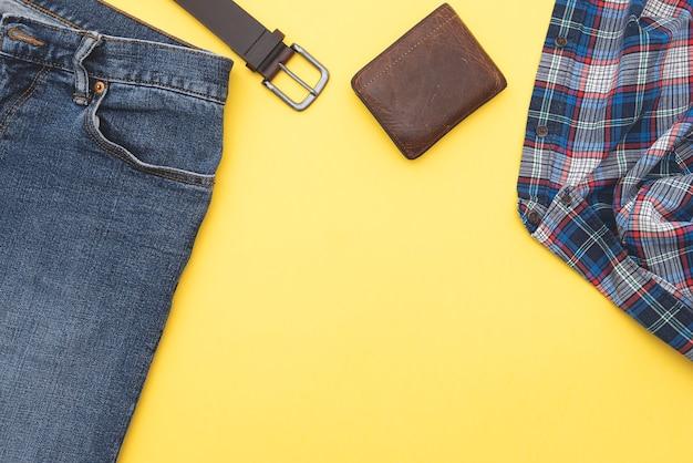 Фон моды, джинсы, рубашка, пояс, бумажник. джинсовый стиль. вид сверху. мужская одежда на желтом фоне, место для текста.