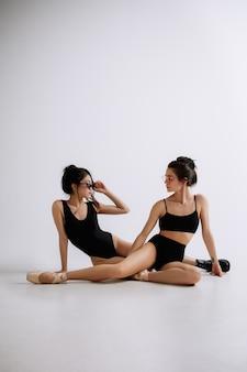 Balletto di moda. due giovani ballerine femminili ballerine caucasiche e asiatiche come modelli di moda. stile, concetto di coreografia contemporanea.