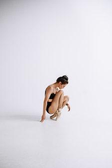 Fashion ballet. young female ballet dancer in black bodysuit against white  wall. caucasian ballerina like a fashion model. style, contemporary choreography concept. creative art photo.