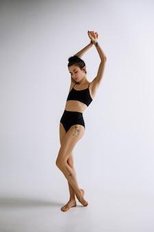 패션 발레. 흰색 배경에 검정 bodysuit에서 젊은 여성 발레 댄서.