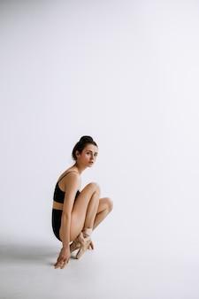 패션 발레. 흰색 스튜디오 배경에 검은 bodysuit에서 젊은 여성 발레 댄서. 패션 모델 같은 백인 발레리나. 스타일, 현대적인 안무 개념. 창의적인 예술 사진.