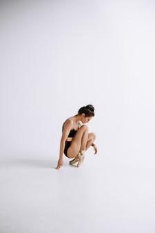 패션 발레. 흰 벽에 검은 bodysuit에서 젊은 여성 발레 댄서. 패션 모델 같은 백인 발레리나. 스타일, 현대적인 안무 개념. 창의적인 예술 사진.