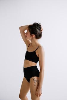 ファッションバレエ。黒のボディースーツを着た若い女性のバレエダンサー。ファッションモデルのような白人バレリーナ。スタイル、現代的な振り付けのコンセプト。