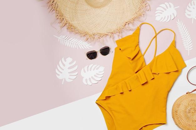 Модная бамбуковая сумка и солнцезащитные очки, соломенная шляпа и купальник. плоская планировка, вид сверху. концепция летних каникул.