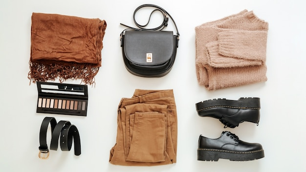 Fashion basic female folded clothes set in beige brown colour outfit. cloth and shoes casual style with knitted sweater.spring winter woman outfit. flat lay clothes cosmetics on white long web banner.