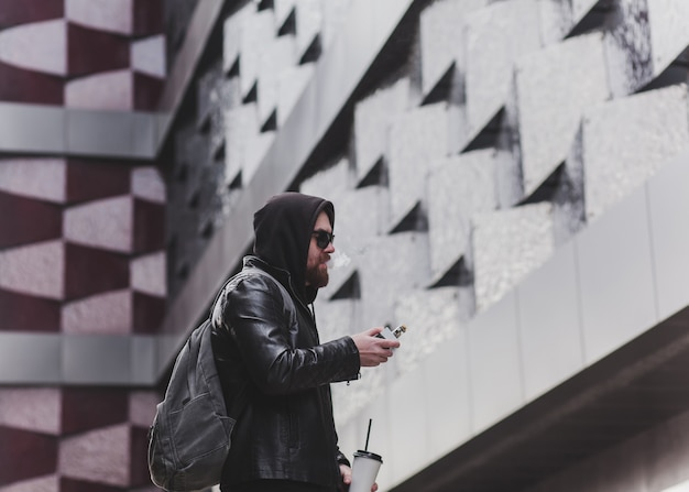 Fashion bearded male dressed in leather jacket, sunglasses and hood vaping. man in holding a mod. a cloud of vapor.