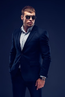 Fashion bearded young serious man in sunglasses luxury suit with one hand in pocket
