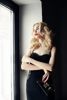 Fashion beautiful blonde woman in sexy tight black dress standing near the window. bright makeup for successful women