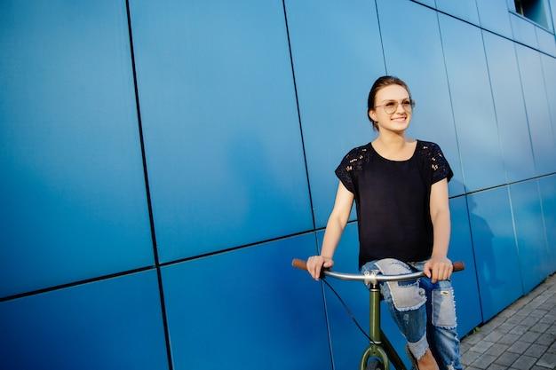 自転車に座って、よそ見と元気に笑顔のサングラスで美しい少女をファッションします。水色の壁に。