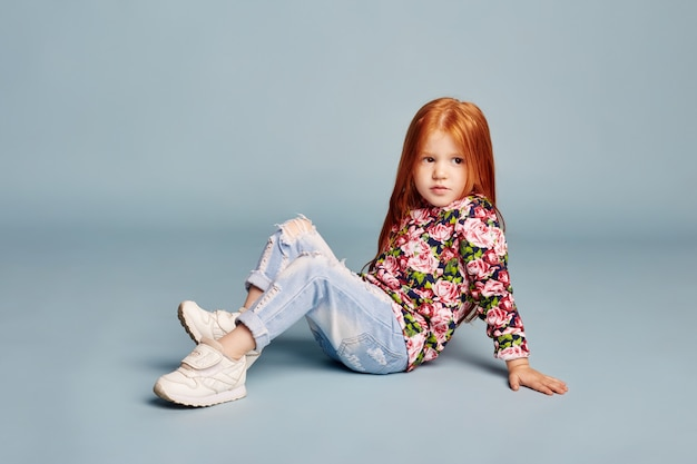 Fashion beautiful girl posing on blue background