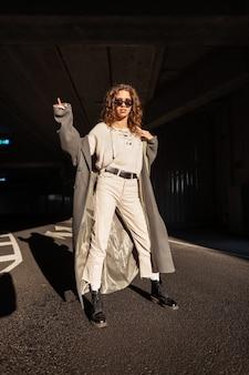스웨터, 바지, 부츠, 선글라스가 달린 세련된 긴 코트에 곱슬머리를 한 아름다운 소녀가 햇빛 아래 도시에서 포즈를 취합니다. 여성스러운 도시 스타일.
