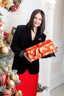 고급스러운 인테리어에 화장을 한 아름다운 관능적인 새해 여성 패션. 크리스마스 트리 조명 배경 위에 빨간 치마와 검은 재킷에 우아한 아가씨. 새해 복 많이 받으세요. 손에 선물