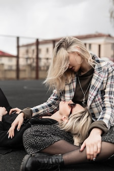 Fashion beautiful sisters in fashionable casual retro clothes sit and look at each other