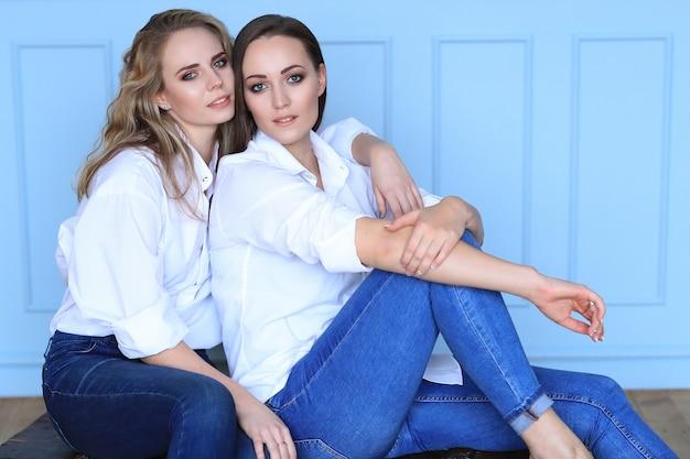 一緒にポーズをとって白いシャツとジーンズの美しい女性をファッション
