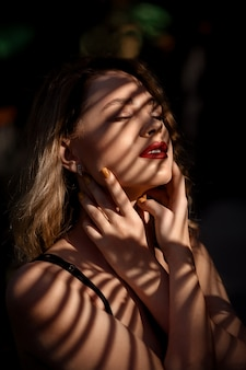 Fashion beautiful woman with sensual red lips posing in shadow stripes on dark