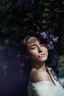 Fashion beautiful young woman surrounded by lilac flowers