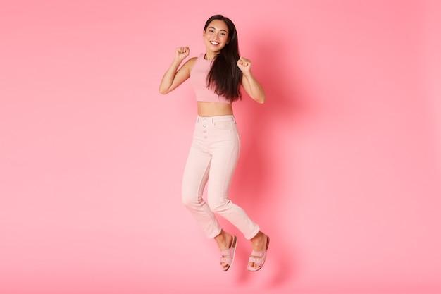 패션, 뷰티 및 라이프 스타일 개념. 평온한 아름 다운 아시아 여자 행복에서 점프, 낙관적이고 편안한 찾고, 휴가를 축하하고, 쇼핑을 즐기고, 분홍색 벽에 서.
