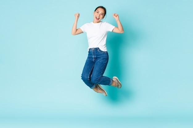패션, 뷰티 및 라이프 스타일 개념. 쾌활한 승리, 행복과 기쁨에서 점프하는 매력적인 아시아 소녀, 경쟁에서 승리하고 밝은 파란색 벽에서 승리를 축하합니다.