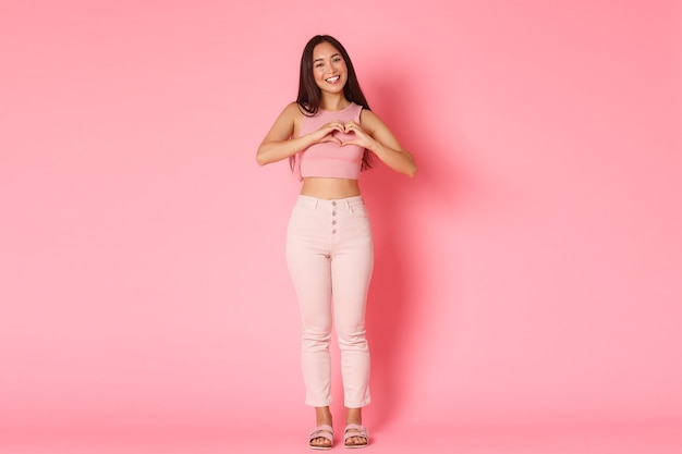 ファッション、美容、ライフスタイルのコンセプトです。ピンクの壁に立って、ハートのジェスチャーを示し、愛、共感、ケアを表現し、グラム服で美しい、コケティッシュなアジアの女の子の完全な長さ。