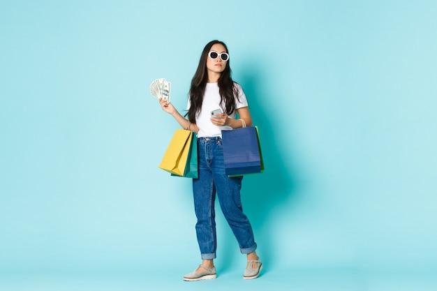 ファッション、美容、ライフスタイルのコンセプト。サングラスをかけた生意気な若いアジア人女性が買い物をしながら周りを見回し、お金を持って、服と携帯電話のバッグ、水色の背景。
