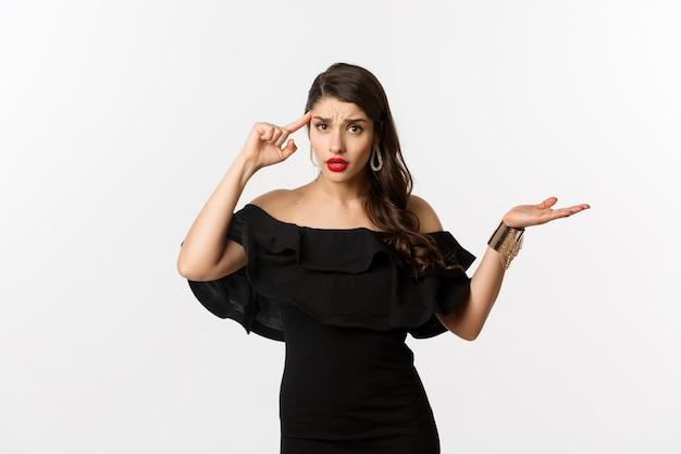 Moda e bellezza. donna infastidita e infastidita che indica la testa, che rimprovera qualcuno per stupido errore, che sembra confusa, in piedi su sfondo bianco.