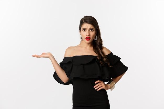 Moda e bellezza. donna infastidita in abito nero alzando la mano, quindi quale gesto, guardando confuso alla telecamera, in piedi infastidito su sfondo bianco.