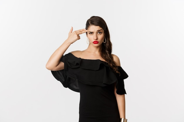 Fashion and beauty. annoyed young woman in black dress making finger gun gesture near head, shooting herself from irritation, standing over white background.