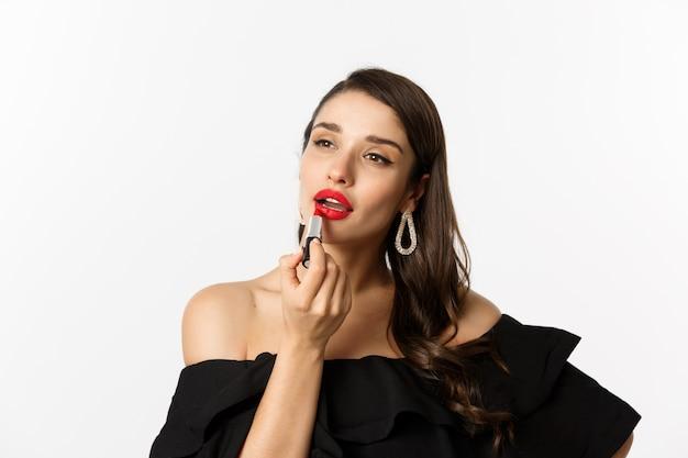 Concetto di moda e bellezza. bella donna in abito nero che applica rossetto rosso e trucco, andando in festa, in piedi su sfondo bianco.