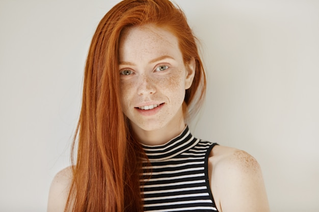 Fashion and beauty concept. charming young female model with long ginger hairstyle and freckles dressed in striped top posing indoors and smiling happily, showing her straight white teeth