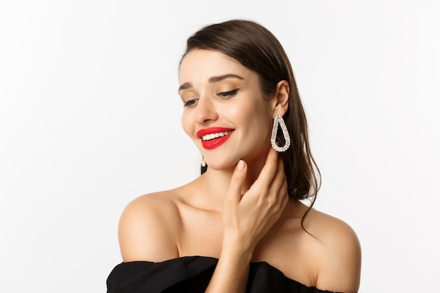 Fashion and beauty concept. close-up of tender woman in black dress and earrings, gently touching face and smiling, looking down coquettish, standing over white background.