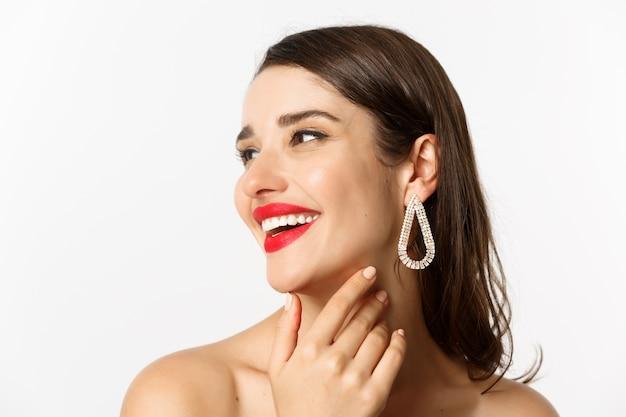 Concetto di moda e bellezza. headshot di splendida donna bruna con rossetto rosso, orecchini, ridendo e guardando a sinistra, in piedi su sfondo bianco.