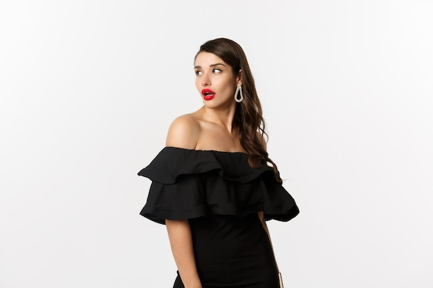 Fashion and beauty concept. image of  young woman in black dress turn behind and looking at copy space, standing over white background.
