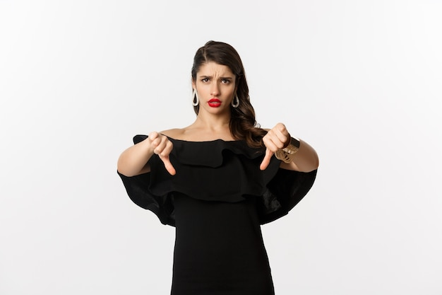 Fashion and beauty. disappointed and upset woman in black dress, showing thumbs down, dislike something bad, judging over white background.