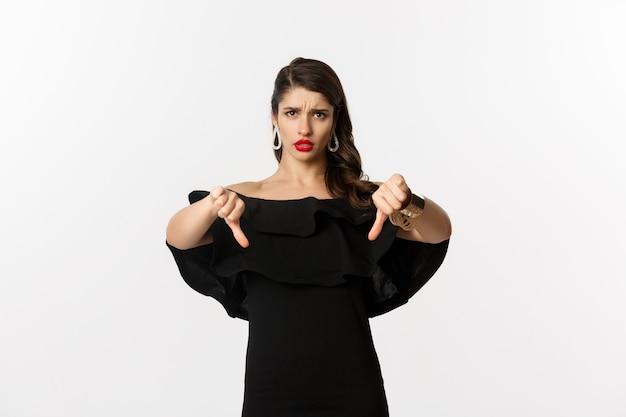 Moda e bellezza. donna delusa e sconvolta in abito nero, che mostra i pollici verso il basso, non mi piace qualcosa di brutto, giudicando su sfondo bianco