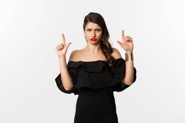 Moda e bellezza. donna delusa che tiene il broncio sconvolta, punta il dito verso l'alto e si lamenta, in piedi insoddisfatta in abito nero, sfondo bianco.