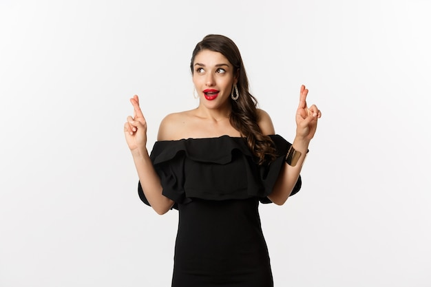 Fashion and beauty. excited gorgeous woman in black dress, holding fingers crossed and looking at upper left corner, making wish, standing over white background.