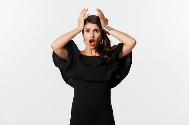 Moda e bellezza. giovane donna frustrata in abito nero, ansimando e tenendosi per mano sulla testa in preda al panico, in piedi preoccupata su sfondo bianco