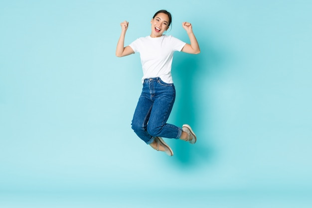Concetto di moda, bellezza e stile di vita. allegra trionfante, attraente ragazza asiatica che salta dalla felicità e dalla gioia, vincendo la concorrenza, celebrando la vittoria sul muro azzurro