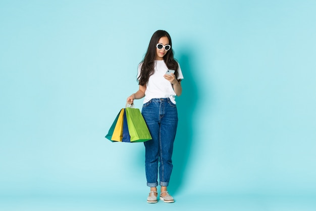Fashion, beauty and lifestyle concept. full-length shot of stylish attractive asian woman holding shopping bags and using mobile phone, texting message over light blue background.