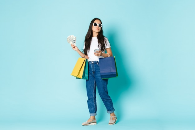 Fashion, beauty and lifestyle concept. sassy young asian woman in sunglasses looking around while shopping, holding money, bags with clothes and mobile phone, light blue background.