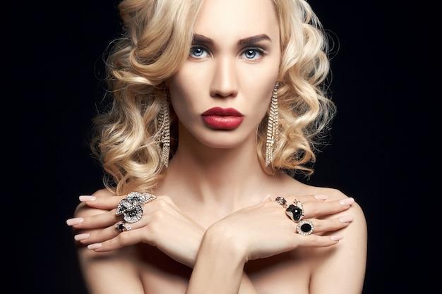 ファッションの美しさ暗い背景に裸のブロンドの女性。腕と首に宝石を持つ少女。スキンケアと美しいメイクの完璧な女の子。エレガントな巻き毛の豪華な女性