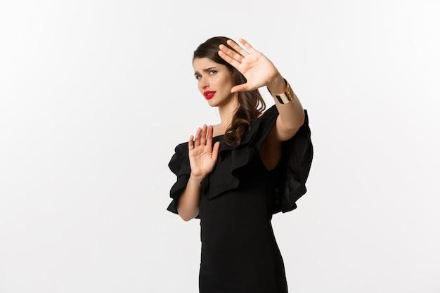 Moda e bellezza. donna riluttante e preoccupata che chiede di stare lontano, mostrando il gesto di arresto e sembra spaventata, in piedi in abito nero su sfondo bianco.