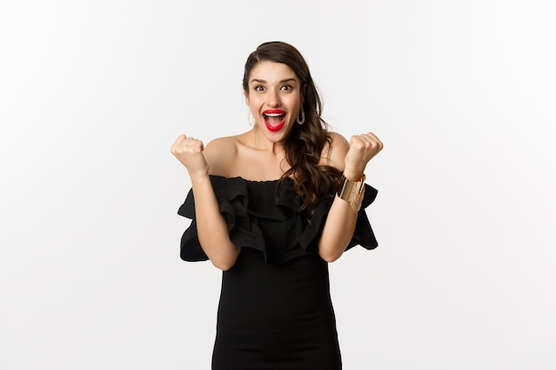Fashion and beauty. successful pretty woman in black dress celebrating, rejoicing of winning, triumphing over white background.