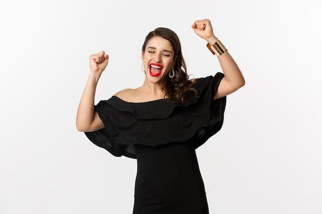 Moda e bellezza. bella donna di successo in abito nero che celebra, si rallegra della vittoria, trionfa su sfondo bianco