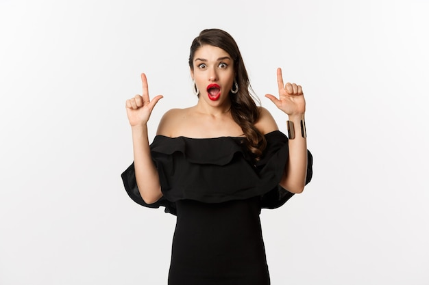 Moda e bellezza. donna sorpresa in abito nero che punta le dita in alto, mostrando banner, in piedi su sfondo bianco