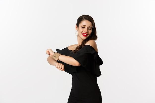 Moda e bellezza. donna che si sente felice e balla in abito da sera nero, in piedi spensierata su sfondo bianco.
